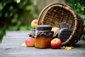 Apple sauce jars and apples spilling out of a wicker basket