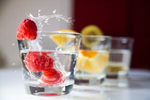 Glasses of water with whole fruits in the water