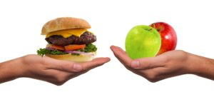 Hands holding out a choice of burger vs two apples