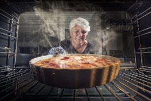 Lady Taking Homemade Apple Pie Out of the Oven