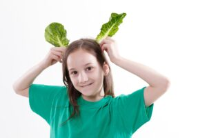 Young girl holding salad leaves as pretend ears