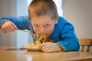 Young boy eating one extra forkful of pasta