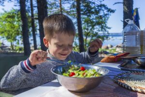 Young boy with big bowl of salad at a picnic table in nature