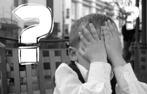 Young child with head in hands surrounded by question marks