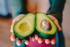 avocado cut in half being offered in open hands