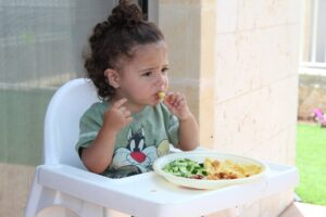 child eating a plate of pasta and vegetables