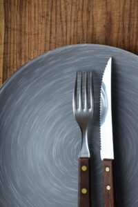 empty plate with knife-and-fork resting on it