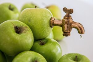 green apples with a tap inserted to demonstrate creating apple juice
