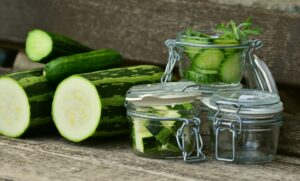selection of zucchini and cucumbers whole and chopped into glass jars
