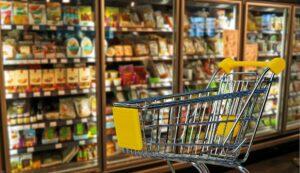 supermarket shopping trolley with shelves of processed food behind
