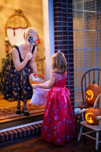 young girl collecting a big bag of halloween candy from a neighbor
