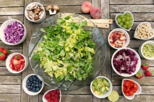Big bowl of salad leaves on a wooden table with many small bowls of other salad items around it