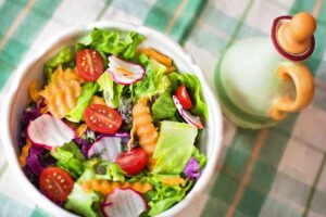 Bowl of salad with tomatoes, radish, carrots and leaves with a dressing jug next to it