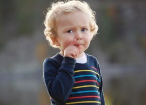 Child with hands in a gesture indicating something small