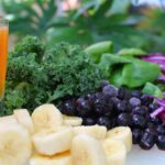 Juiced or blended fruit and vegetable drink surrounded by berries, bananas, kale, spinach and cabbage