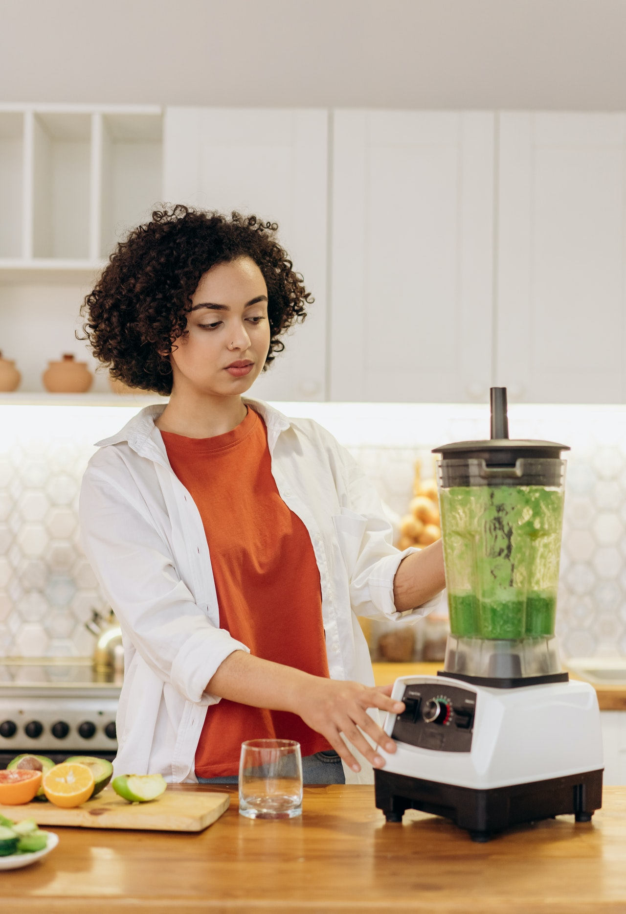 Lady making a green smoothie in a blender in her kitchen