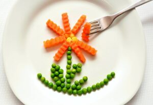 Peas, carrots and sweetcorn shaped into a flower on a white plate