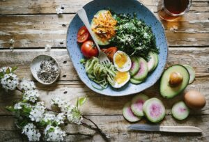 Plate of various vegetables, salad eggs, tomatoes and avocado on a wooden table