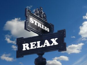Stress and Relax signs facing opposite direction with a blue sky with fluffy clouds behind