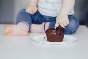 Toddler sticking finger into the center of a chocolate cupcake