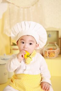 Young boy in chefs outfit trying a yellow pepper