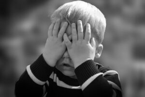Young boy with hands over his eyes