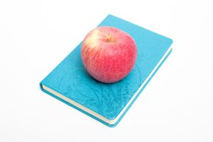 apple sitting on top of journal to plan snacks