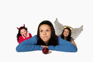 girl thinking whether to eat the apple in front of her with a devil and angel of each shoulder