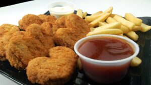 plate of chicken nuggets with chips and tomato sauce