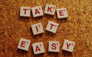 take it easy spelled out with scrabble pieces on a cork board