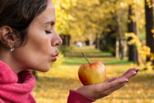 woman blowing a kiss lovingly to an apple in her hand